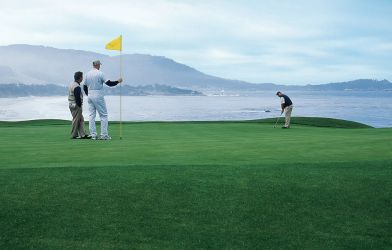 Three players on the green at Pebble Beach with the ocean in the background